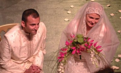 Image of an Indian French couple, kneeling on the stage in white wedding clothes, getting married