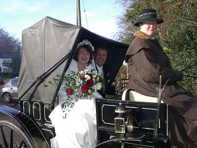 Image of Issy and Andy after their ceremony, in the back of a horse and cart. Issy in a white dress with a huge bouquet of flowers on her lap