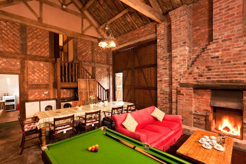 Inside view of Broomfield barn. A red sofa, a pool table, a long rectangle dining table, a fire place all within red brick walls, and a high ceiling